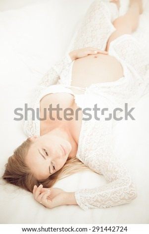Pregnant woman lying on the bed - stock photo