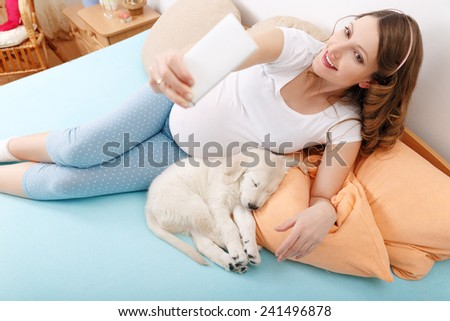 Pregnant woman making selfie shoot with her dog - stock photo