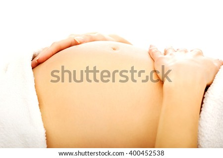 Pregnant woman massagin her belly - stock photo
