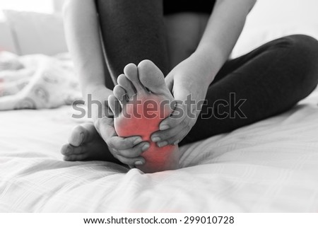 Pregnant woman massaging her painful foot, red hi-lighted on pain area - stock photo