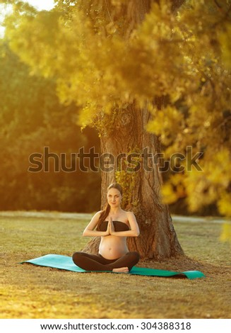 Pregnant woman meditating under a tree.looking straight ahead - stock photo