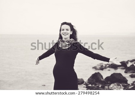 pregnant woman near the sea in spring - stock photo