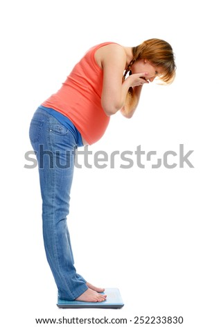 Pregnant woman on scales surprised by its weight, isolated on white - stock photo