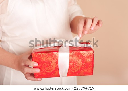 Pregnant woman opening christmas box over beige closeup