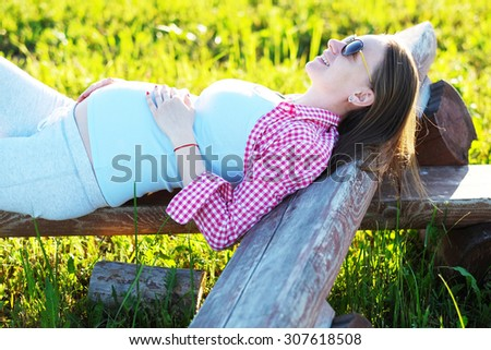 Pregnant woman outdoors at sunny summer day - stock photo