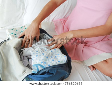 Pregnant woman packing baby clothes for going to hospital.