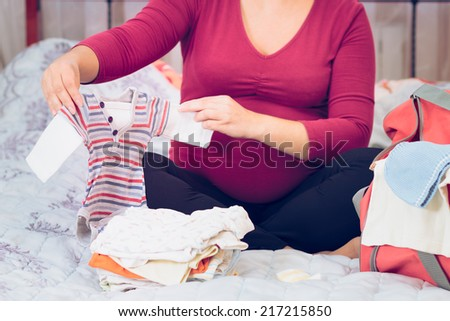 Pregnant woman packing hospital bag preparing for labor - stock photo