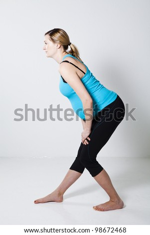 Pregnant woman performing a leg stretching exercise for the hamstring muscles