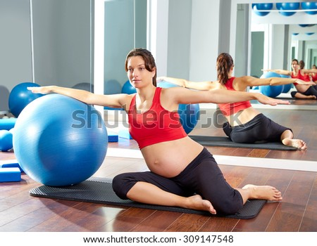 pregnant woman pilates mermaid fitball exercise workout at gym indoor - stock photo