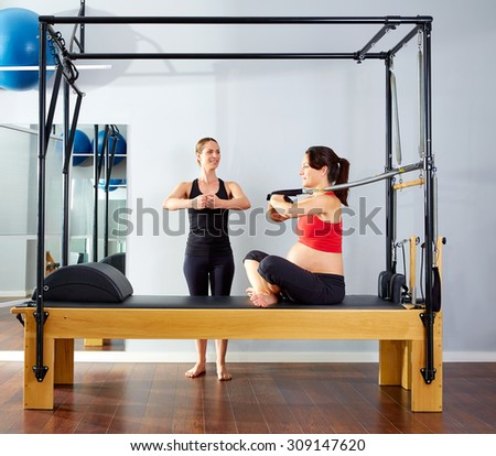 pregnant woman pilates reformer cadillac arms exercise workout with personal trainer - stock photo