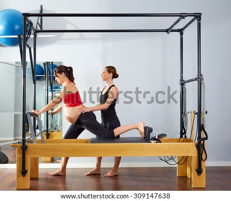 pregnant woman pilates reformer cadillac exercise workout with personal trainer - stock photo