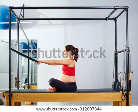 pregnant woman pilates reformer forward push through exercise workout at gym - stock photo