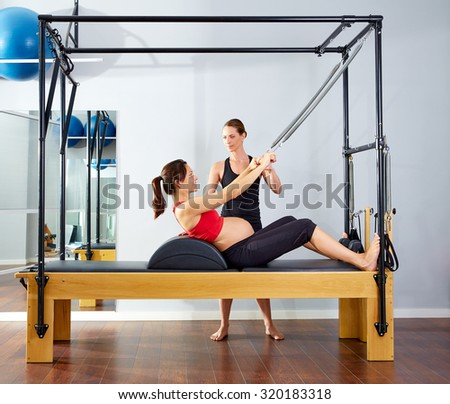 pregnant woman pilates reformer roll up cadillac exercise with personal trainer