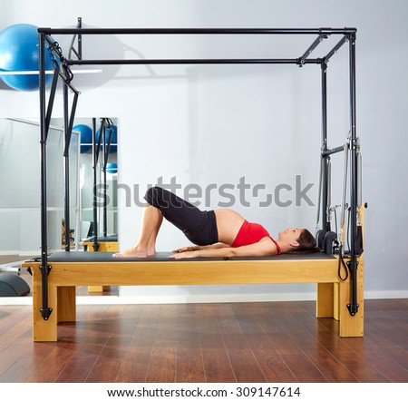 pregnant woman pilates reformer shoulder bridge  exercise workout at gym - stock photo