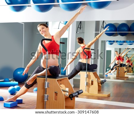 pregnant woman pilates side stretch exercise on wunda chair at gym indoor - stock photo