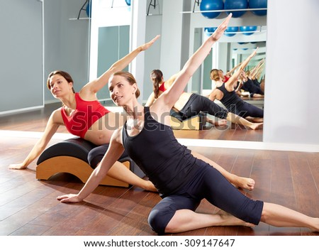 pregnant woman pilates side stretching exercise with Wave corrector and personal trainer