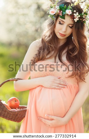 Pregnant woman posing in a green apple garden with apple in her hands. Young pregnant woman relaxing in park outdoors, healthy pregnancy. Beautiful pregnant woman holding her tummy. - stock photo