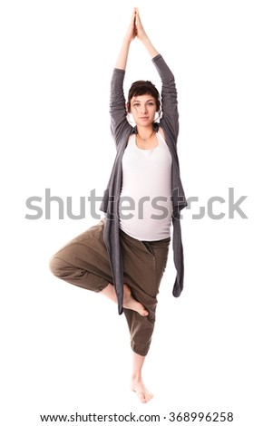 Pregnant woman practicing yoga, free gray casual clothing, white background - stock photo