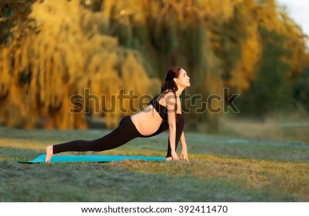 Pregnant woman practicing yoga in the park