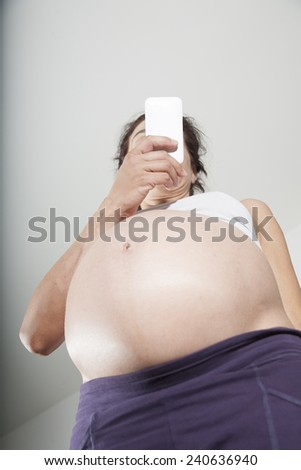pregnant woman purple trousers bare belly watching smartphone - stock photo