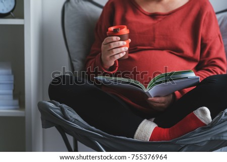 Pregnant woman reading book about pregnancy and maternity in living room