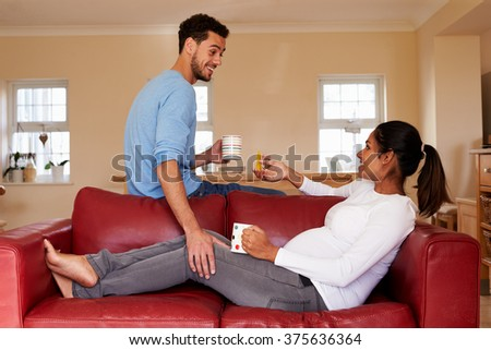 Pregnant Woman Relaxes On Sofa With Husband - stock photo