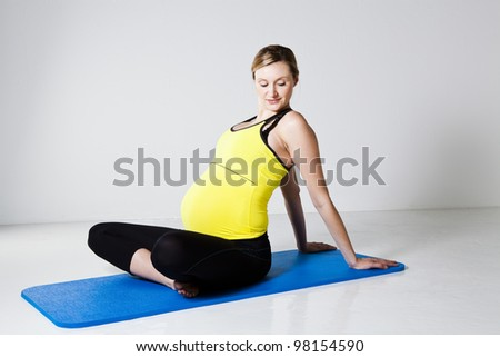 Pregnant woman relaxing on a mat and stretching her trunk and upper arms - stock photo