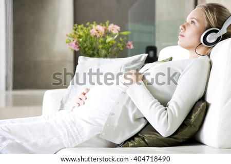 Pregnant woman relaxing whilst listening to music on headphones - stock photo