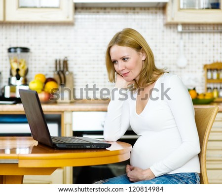 pregnant woman relaxing with her laptop in her kitchen - stock photo