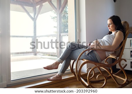 Pregnant woman resting at home - stock photo
