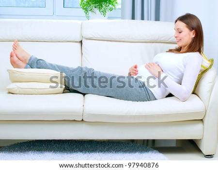 Pregnant Woman Resting On Sofa...