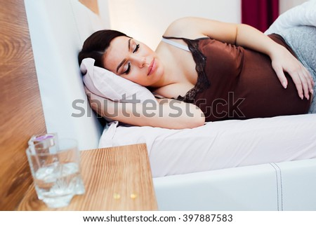 Pregnant woman resting with pills at hand for various aches