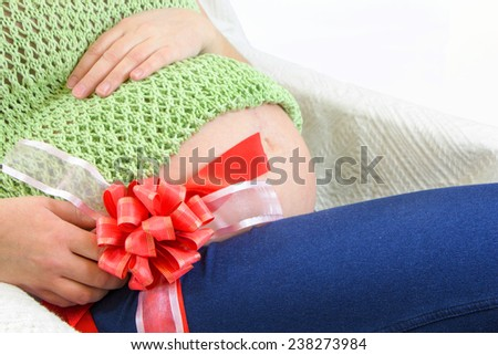 Pregnant woman's cute belly with big red ribbon - stock photo