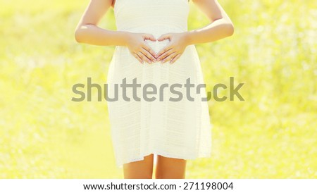 Pregnant woman showing hands in shape heart on belly in sunny summer day - stock photo