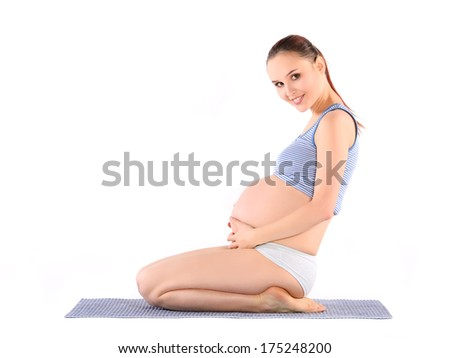 Pregnant woman siting on the floor and hugs her tummy - stock photo