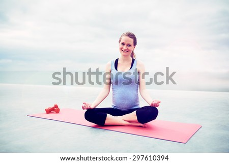 Pregnant woman sitting in the lotus position meditating on an exercise mat looking at the camera with a serene expression and lovely warm smile - stock photo