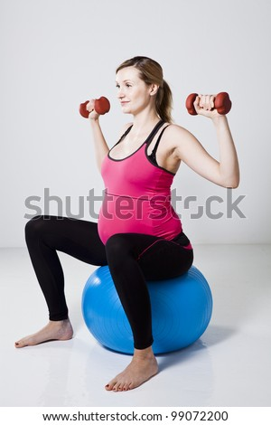 Pregnant woman sitting on a fitness ball and exercising the shoulder muscles with dumbbells - stock photo