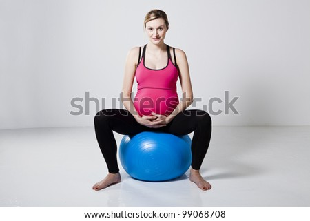 Pregnant woman sitting on a fitness ball and relaxing - stock photo