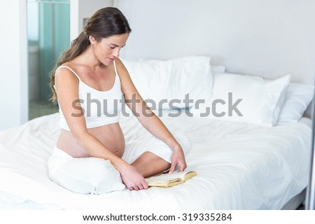 Pregnant woman sitting on bed reading novel