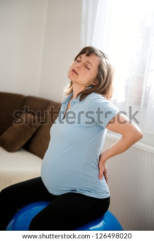 Pregnant woman sitting on fit ball with backache at home - stock photo