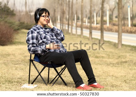 Pregnant woman sitting on lawn listens music under warm sunshine in early spring.