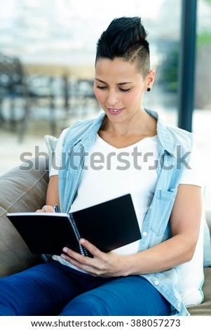Pregnant woman sitting on sofa and writing on notepad
