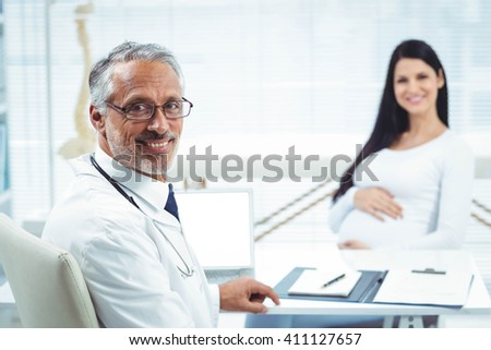 Pregnant woman sitting with doctor at clinic for health checkup