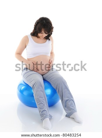 pregnant woman sitting with exercise bal. Isolated on white background