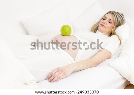 pregnant woman sleeping in bed with a green apple - stock photo