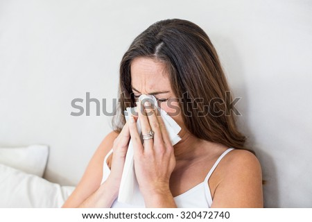 Pregnant woman sneezing with tissue on mouth in bedroom