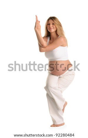 Pregnant woman standing and practicing yoga isolated on white - stock photo