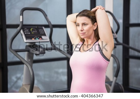 Pregnant woman stretching at the gym