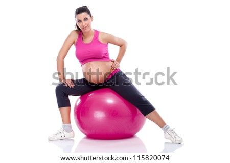 Pregnant woman stretching legs while sitting on fitness ball - stock photo