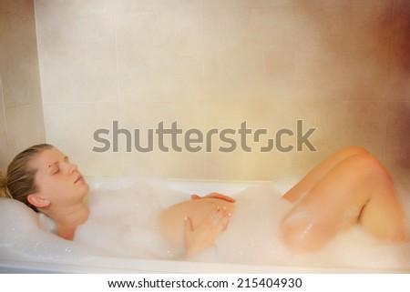 Pregnant woman taking spa bath - stock photo